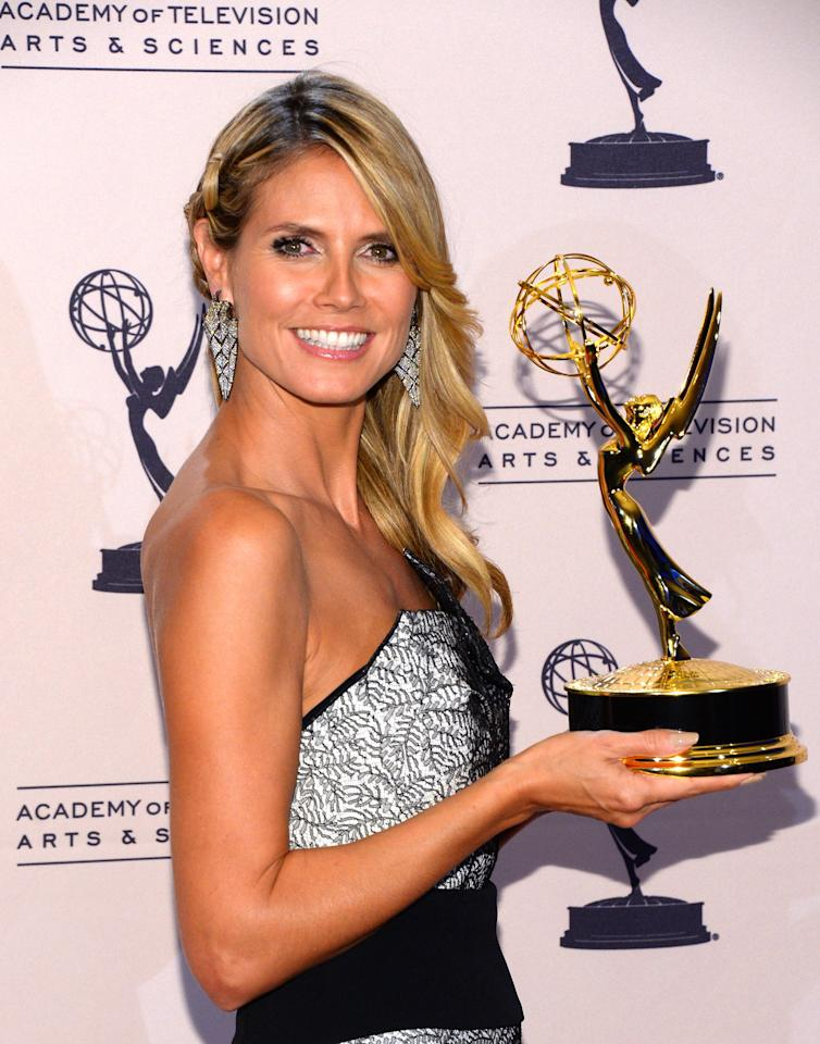 "LOS ANGELES, CA - SEPTEMBER 15: Television host Heidi Klum poses with the award for outstanding host for a reality or reality-competition program for ""Project Runway"" at the Primetime Creative Arts Emmy Awards held at the Nokia Theatre L.A. Live on September 15, 2013 in Los Angeles, California. (Photo by Mark Davis/Getty Images)"