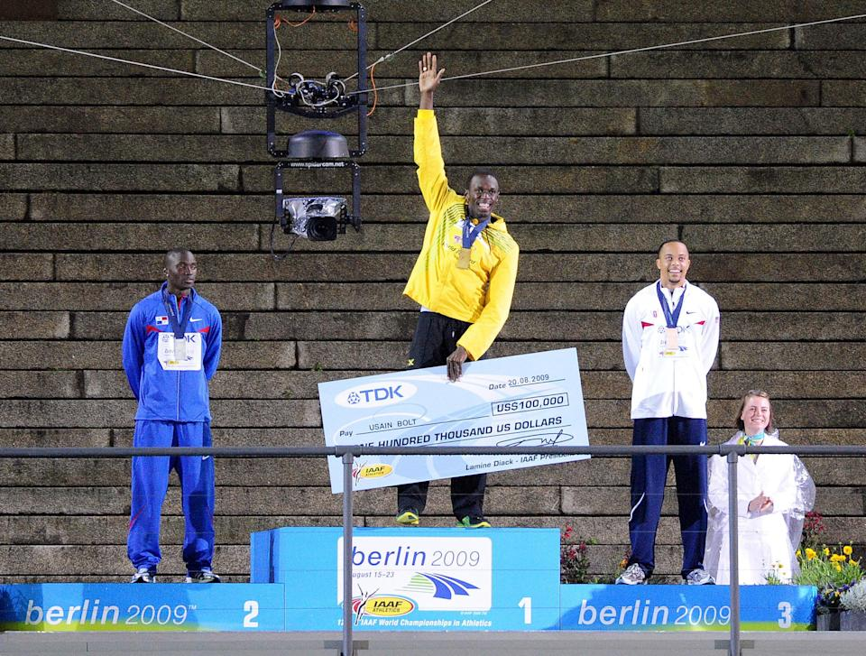 Usain Bolt jumps onto the platform tonight as he receives his Gold Medal for the 200m Event he won last night during the IAAF World Championships at the Olympiastadion, Berlin.