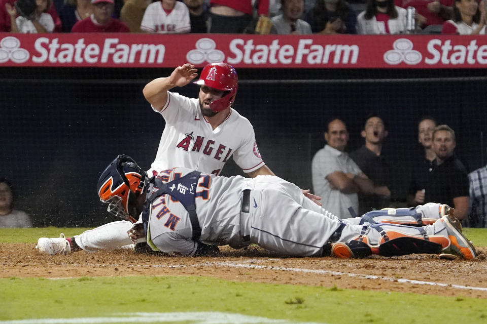 Los Angeles Angels' Jack Mayfield, top, is tagged out at home by Houston Astros catcher Martin Maldonado while trying to score after Jose Rojas was safe at first on a fielding error by second baseman Jose Altuve during the sixth inning of a baseball game Thursday, Sept. 23, 2021, in Anaheim, Calif. (AP Photo/Mark J. Terrill)