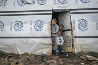 Internally displaced people stand at the entrance of a shelter at the Azezo camp
