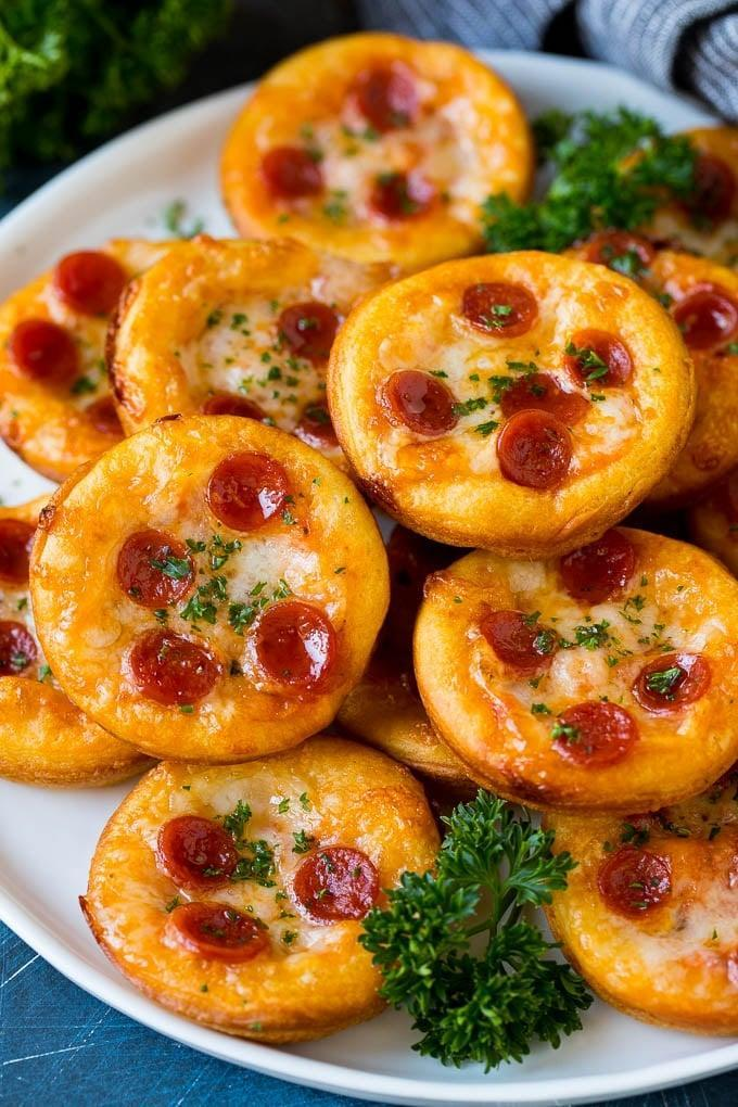 """<p>Made with crescent roll dough and topped with sauce, cheese, and the toppings of your desire, these mini bites will be your new favorite food. They're easy to make and even easier to eat, so be sure to make extra. We suggest making about four or five pizzas if you want to feed two people. Enjoy!</p> <p><strong>Get the recipe:</strong> <a href=""""https://www.dinneratthezoo.com/mini-pizzas/"""" class=""""link rapid-noclick-resp"""" rel=""""nofollow noopener"""" target=""""_blank"""" data-ylk=""""slk:mini pizzas"""">mini pizzas</a></p>"""