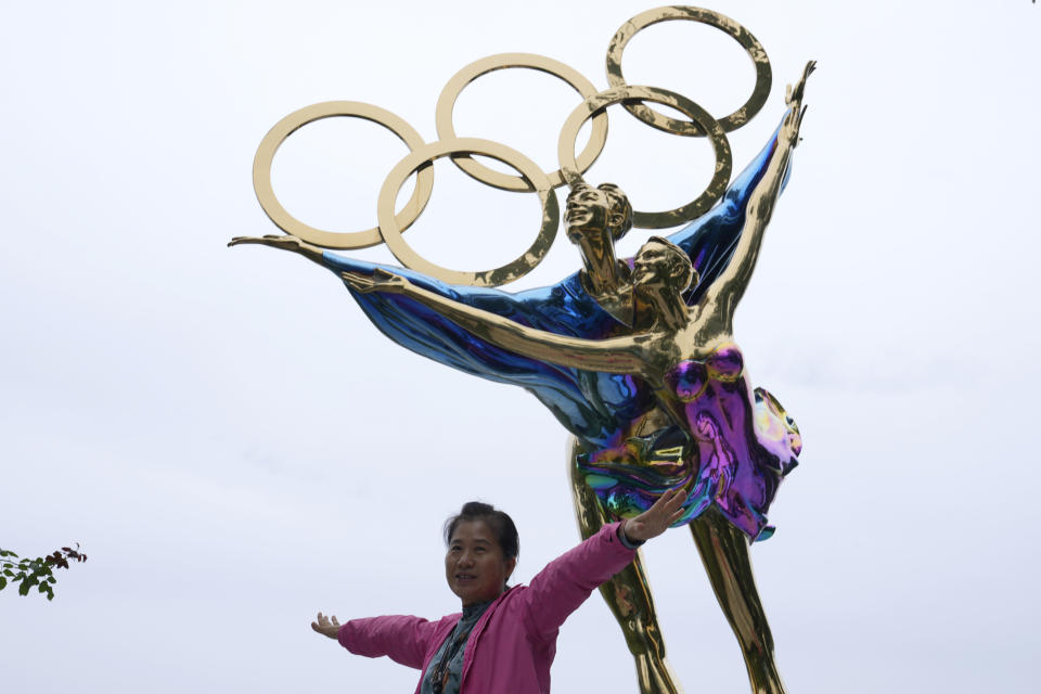 A visitor to the Shougang Park pose for photos in front of a sculpture depicting figure skaters and the Olympic Rings in Beijing Monday, Oct. 4, 2021. When the International Olympic Committee awarded Beijing the 2008 Summer Olympics, it promised the Games could improve human rights and civil liberties in China. (AP Photo/Ng Han Guan)