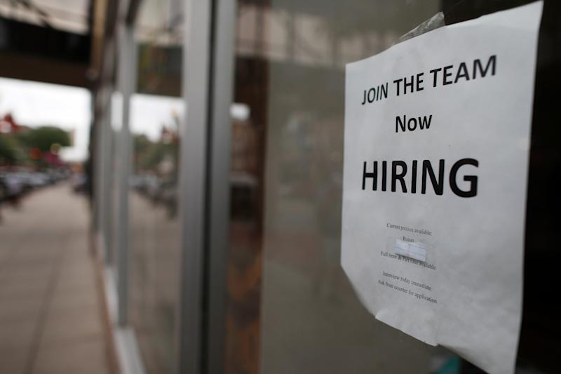 """A """"now hiring"""" sign hangs in the window of a Chinese restaurant in downtown Fargo, N.D. Data shows that small businesses are hiring less, despite the strong economy, partly because they are losing employees to bigger firms."""