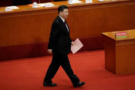Chinese President Xi Jinping walks with his ballot before a vote at the fifth plenary session of the National People's Congress (NPC) at the Great Hall of the People in Beijing, China March 17, 2018.  REUTERS/Jason Lee