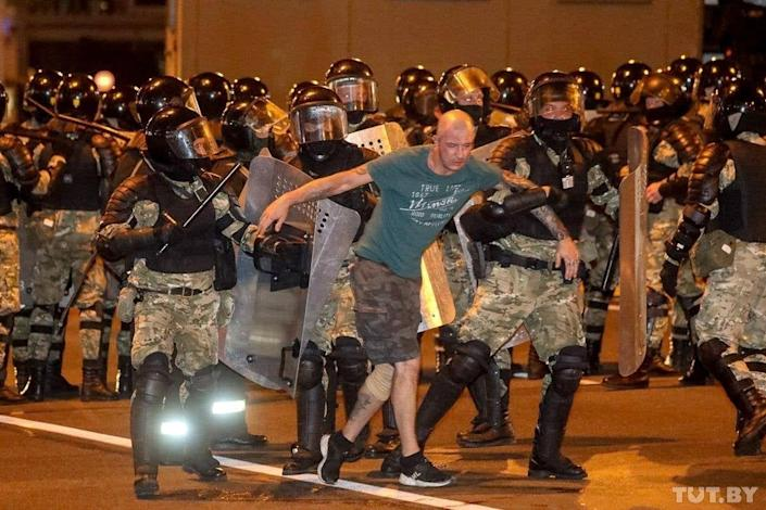 Law enforcement officers escort a man during clashes with opposition supporters in Minsk: via REUTERS