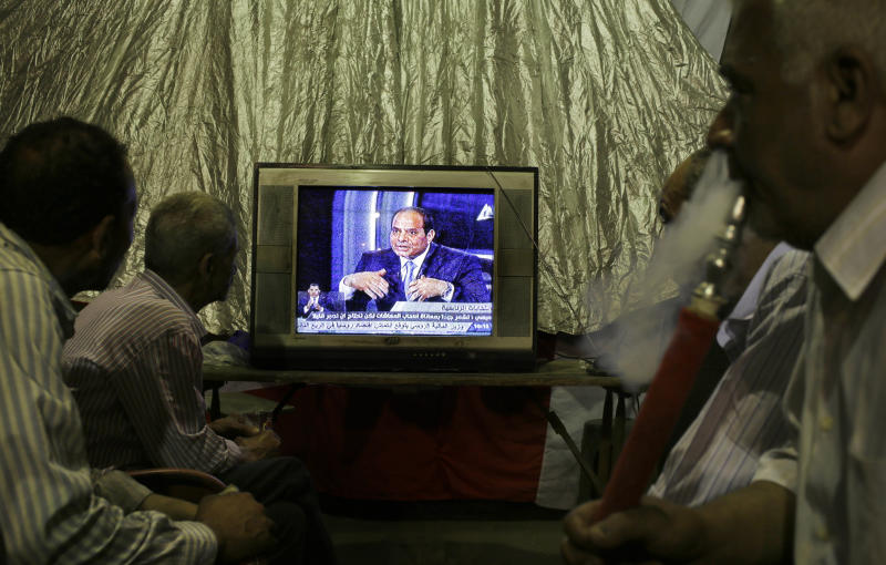 Egyptians smoke traditional water pipes as they watch a televised interview of former army chief Abdel-Fattah el-Sissi at a coffee shop in downtown Cairo, Egypt, late Tuesday, May 6, 2014. El-Sissi gave a TV interview of his campaign to become Egypt's next president , saying he decided to run because of the threats facing the nation after his removal of the country's first democratically elected president, Islamist Mohammed Morsi. (AP Photo/Amr Nabil)