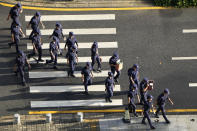 Security personnel march to their duty outside the Evergrande headquarters in Shenzhen, China, Friday, Sept. 24, 2021. Things appeared quiet at the headquarters of the heavily indebted Chinese real estate developer Evergrande, one day after the day it had promised to pay interest due to bondholders in China.(AP Photo/Ng Han Guan)