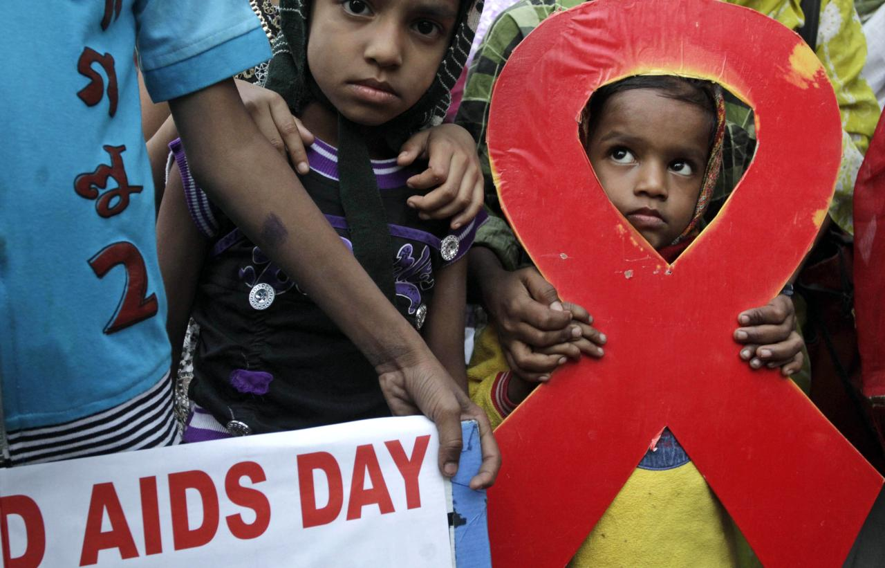 Children walk with activists in a torch light rally ahead of World AIDS Day in Kolkata, India, Friday, Nov. 30, 2012. The activists demanded monthly pension and free ration facilities for sex workers and HIV/AIDS affected people. (AP Photo/Bikas Das)