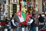 A shop in Amman where people handle a kite with a Jordanian national flag design