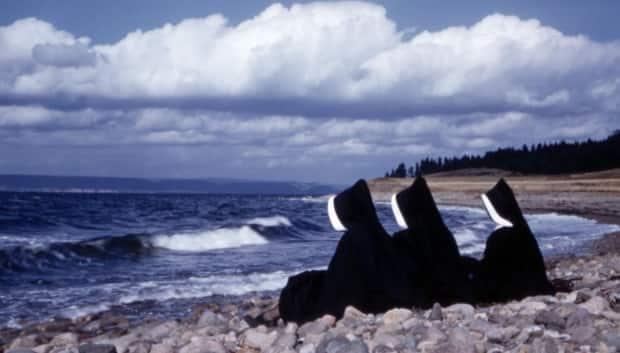 Three Sisters of Charity watch the ocean in this 1957 photo. Members of the organization ran the Shubenacadie institute at the time. (Halifax Congregational Archives - image credit)
