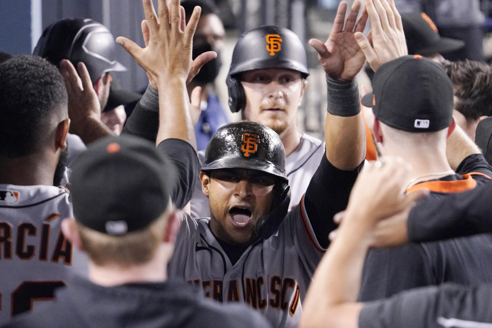 San Francisco Giants' Donovan Solano is congratulated by teammates in the dugout after scoring on a double by Thairo Estrada during the seventh inning of a baseball game against the Los Angeles Dodgers Monday, July 19, 2021, in Los Angeles. (AP Photo/Mark J. Terrill)