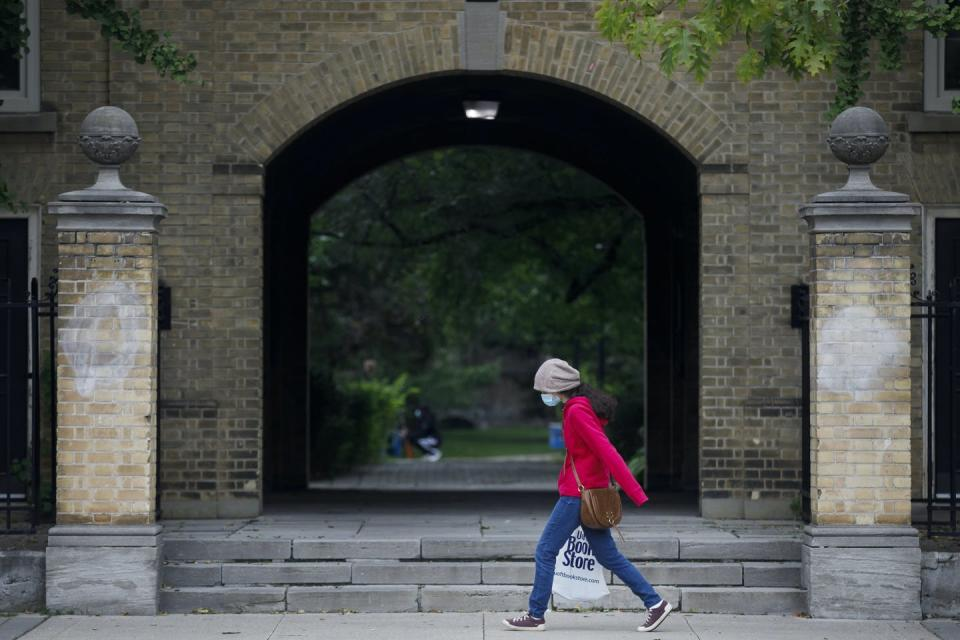 A person walks by carrying a university building.