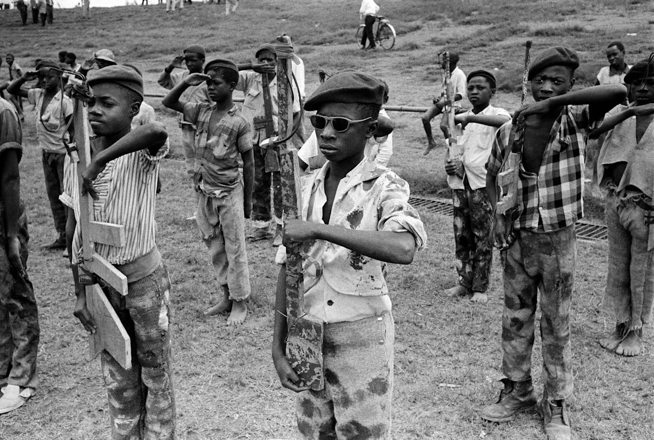FILE - In this Nov. 28, 1961 file photo taken by Associated Press photographer Horst Faas, boys belonging to the Katangese Youth Movement, wearing improvised uniforms of their own design, drill with homemade wooden rifles in the native quarter of Elisabethville, Congo. Faas, a prize-winning combat photographer who carved out new standards for covering war with a camera and became one of the world's legendary photojournalists in nearly half a century with The Associated Press, died Thursday May 10, 2012. He was 79. (AP Photo/Horst Faas, File)
