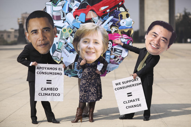 """Activists wearing masks depicting President Barack Obama, left, Germany's Chancellor Angela Merkel, center, and Japan's Prime Minister Naoto Kan protest  world environmental policies in Mexico City, Wednesday Dec. 1, 2010.  Stuck in a blame game led by """"big players"""" U.S. and China, the rest of the world should take on the climate crisis more aggressively """"with or without them,"""" said Mexican President Felipe Calderon during the annual UN Climate Change Conference being held in Cancun, Mexico. (AP Photo/Alexandre Meneghini)"""