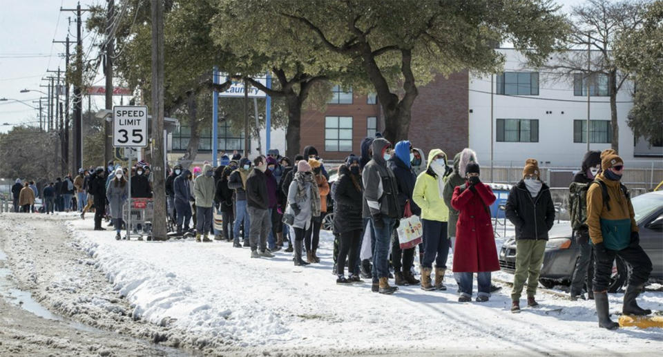People wait in a long line to buy groceries during the extreme cold snap. Source: AP