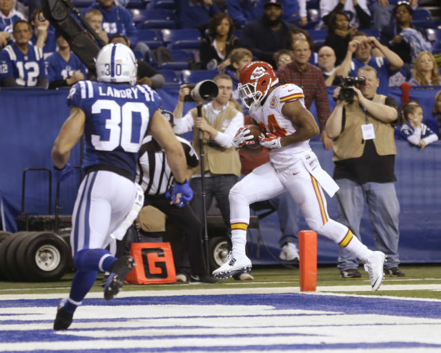 Kansas City Chiefs' Knile Davis (34) makes a 10-yard touchdown reception as Indianapolis Colts strong safety LaRon Landry (30) moves in during the second half of an NFL wild-card playoff football game Saturday, Jan. 4, 2014, in Indianapolis. (AP Photo/Michael Conroy)
