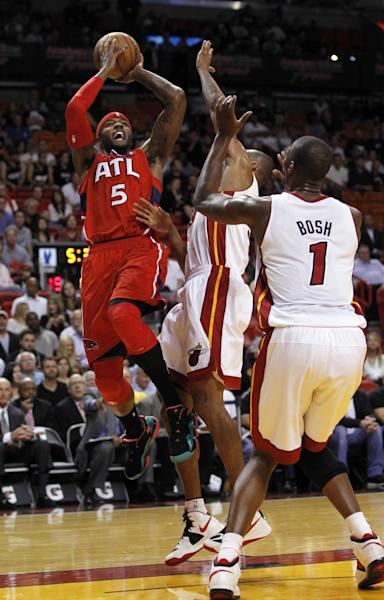 Atlanta Hawks' Josh Smith (5) prepares to shoot over Miami Heat's Shane Battier, center, and Chris Bosh in the first half of an NBA basketball game, Monday, Dec, 10, 2012, in Miami. (AP Photo/Alan Diaz)
