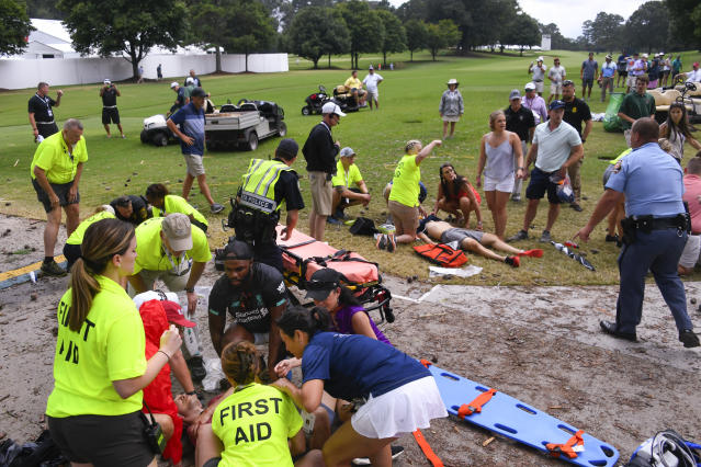 Spectators are tended to after a lightning strike on the East Lake Golf Club course left several injured during a weather delay in the third round of the Tour Championship golf tournament Saturday, Aug. 24, 2019, in Atlanta. (AP Photo/John Amis)