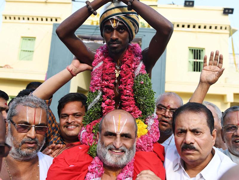 Hindu priest CS Rangarajan carries Dalit devotee Aditya Parasri on his shoulders (Getty)
