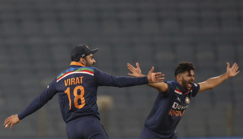 India's captain Virat Kohli, left, and Shardul Thakur appeal for the wicket for England's captain Jos Buttler during the third One Day International cricket match between India and England at Maharashtra Cricket Association Stadium in Pune, India, Sunday, March 28, 2021. (AP Photo/Rafiq Maqbool)