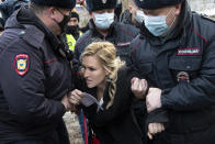 Police officers detain the Alliance of Doctors union's leader Anastasia Vasilyeva at the prison colony IK-2, which stands out among Russian penitentiary facilities for its particularly strict regime, in Pokrov in the Vladimir region, 85 kilometers (53 miles) east of Moscow, Russia, Tuesday, April 6, 2021. Doctors from the Navalny-backed Alliance of Doctors announced going to the Pokrov prison on Tuesday to demand the opposition leader gets qualified medical help from independent doctors after he complained about pain in his leg and back. (AP Photo/Pavel Golovkin)
