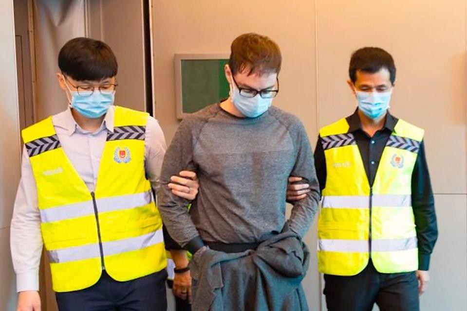 David James Roach being escorted by police officers after arriving in Singapore on 17 March 2020. (Photo: Singapore Police Force)