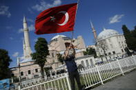 A man waves a Turkish flag outside the Byzantine-era Hagia Sophia, one of Istanbul's main tourist attractions in the historic Sultanahmet district of Istanbul, following Turkey's Council of State's decision, Friday, July 10, 2020.Turkey's highest administrative court issued a ruling Friday that paves the way for the government to convert Hagia Sophia - a former cathedral-turned-mosque that now serves as a museum - back into a Muslim house of worship. The Council of State threw its weight behind a petition brought by a religious group and annulled a 1934 cabinet decision that changed the 6th century building into a museum. (AP Photo/Emrah Gurel)