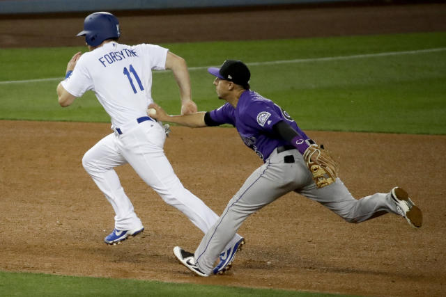 Colorado Rockies shortstop Daniel Castro, right, tags Los Angeles Dodgers' Logan Forsythe in a rundown during the fourth inning of a baseball game in Los Angeles, Wednesday, May 23, 2018. (AP Photo/Chris Carlson)