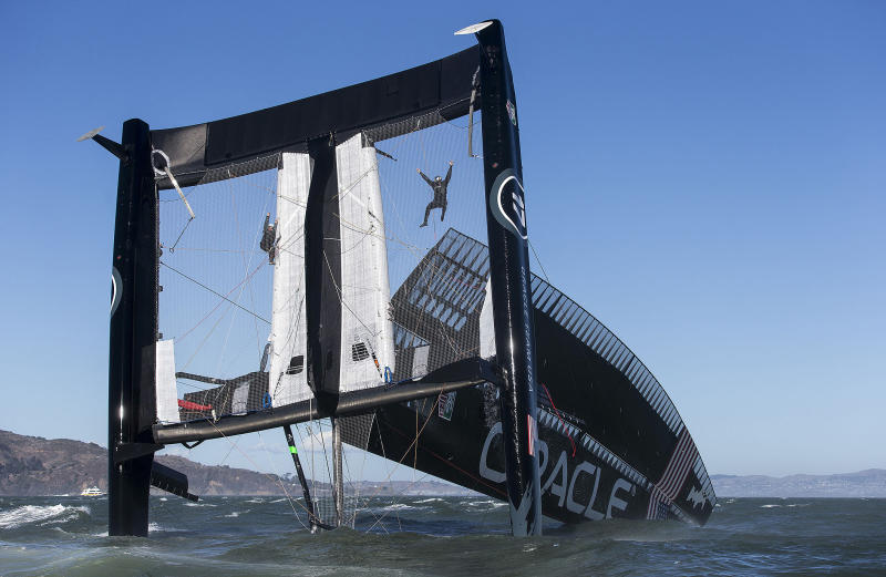 In this photo taken Tuesday Oct. 16, 2012 and provided by Oracle Team USA, crew members hang from the mesh netting after the Oracle Team USA AC72 boat capsized on San Francisco Bay in San Francisco. The America's Cup champion syndicate is assessing the damage to its 72-foot (22-meter) catamaran, after it capsized and was swept by a strong current more than four miles (six kilometers) past the Golden Gate Bridge before rescue boats could control it.(AP Photo/Oracle Team USA, Guilain Grenier) MANDATORY CREDIT