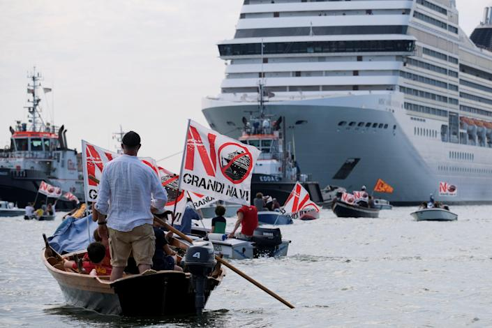 """This image shows people on small boats with signs that say """"NO"""" headed towards a large cruiseship"""