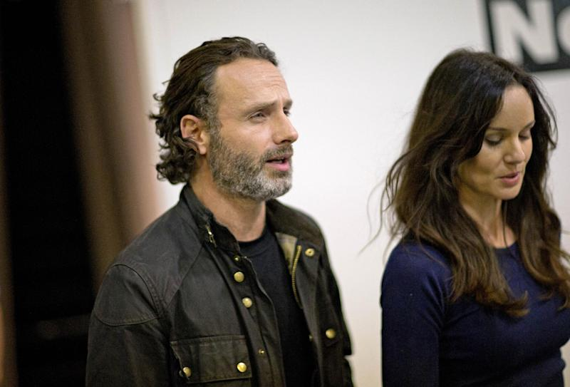 "Andrew Lincoln, left, who plays Rick Grimes on the cable TV show ""The Walking Dead,"" walks through Walker Stalker Con, a convention based off the show, with fellow cast member Sarah Wayne Callies, right, Saturday, Nov. 2, 2013, in Atlanta. For Lincoln, acting out the battle scenes in downtown Atlanta during the first season of ""The Walking Dead"" was a joyous time. Here was the British actor, on the same streets where Confederate forces battled Union troops in the American Civil War, shooting his way through a foreboding urban landscape now over-run by flesh-devouring ""walkers."" ""It was one of the greatest weekends of my career, you know,"" he says, his eyes lighting up with excitement. ""We shut down four blocks of downtown Atlanta and I get to ride into the city on a horse. It was epic. (AP Photo/David Goldman)"