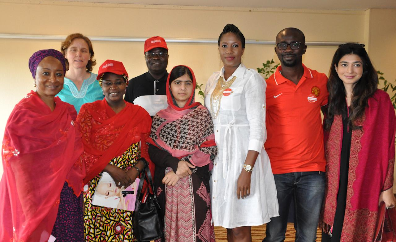 Pakistani activist Malala Yousafzai, who survived being shot by the Taliban because she advocated education for girls, poses for a photograph with the organizers of Bring Back Our Girls campaign, in Abuja, Nigeria, Sunday July 13, 2014. Malala Yousafzai traveled to Abuja in Nigeria to meet the relatives of schoolgirls who were kidnapped by Boko Haram three months ago. (AP Photo/Olamikan Gbemiga)