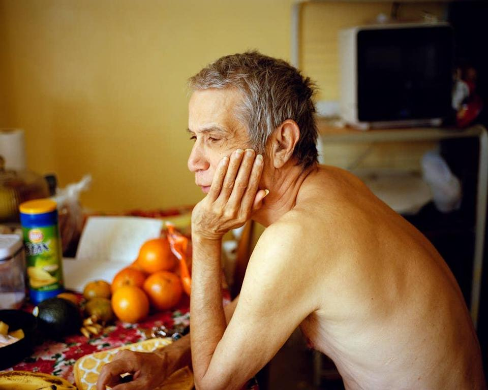 A man sitting shirtless at a table with oranges and potato chips on it
