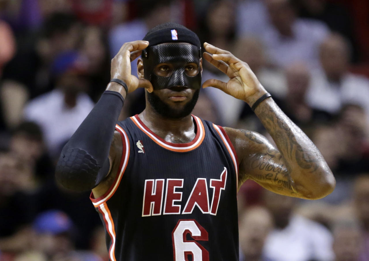 Miami Heat small forward LeBron James (6) adjusts his mask during the first half of an NBA basketball game against the New York Knicks in Miami, Thursday, Feb. 27, 2014. (AP Photo/Alan Diaz)