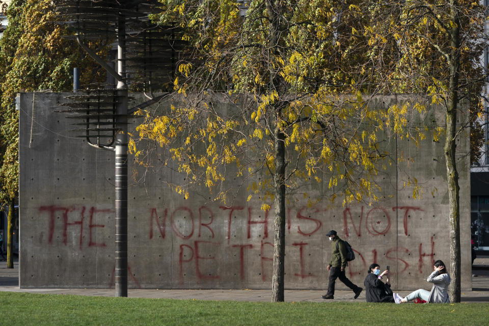 A man walks past graffiti referring to coronavirus, in Manchester city centre, England, Tuesday Oct. 20, 2020. The UK government has adopted a three-tier system for England, with areas classed as medium, high of very high risk. So far, only the Liverpool and Lancashire regions of northwest England have been placed in the highest tier. Nearby Greater Manchester, with a population of almost 3 million, has been holding out for more support for workers and businesses affected by the restrictions. (AP Photo/Jon Super)