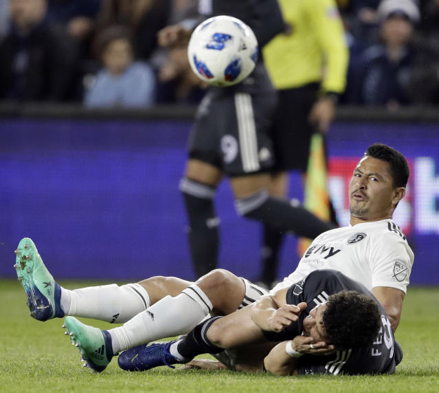 Sporting Kansas City midfielder Roger Espinoza, top, lands on Vancouver Whitecaps midfielder Felipe Martins (8) during the first half of an MLS soccer match in Kansas City, Kan., Friday, April 20, 2018. (AP Photo/Orlin Wagner)