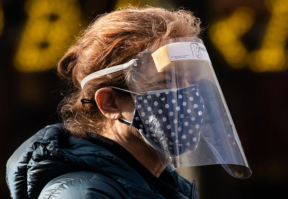 A woman wears a face mask and shield.