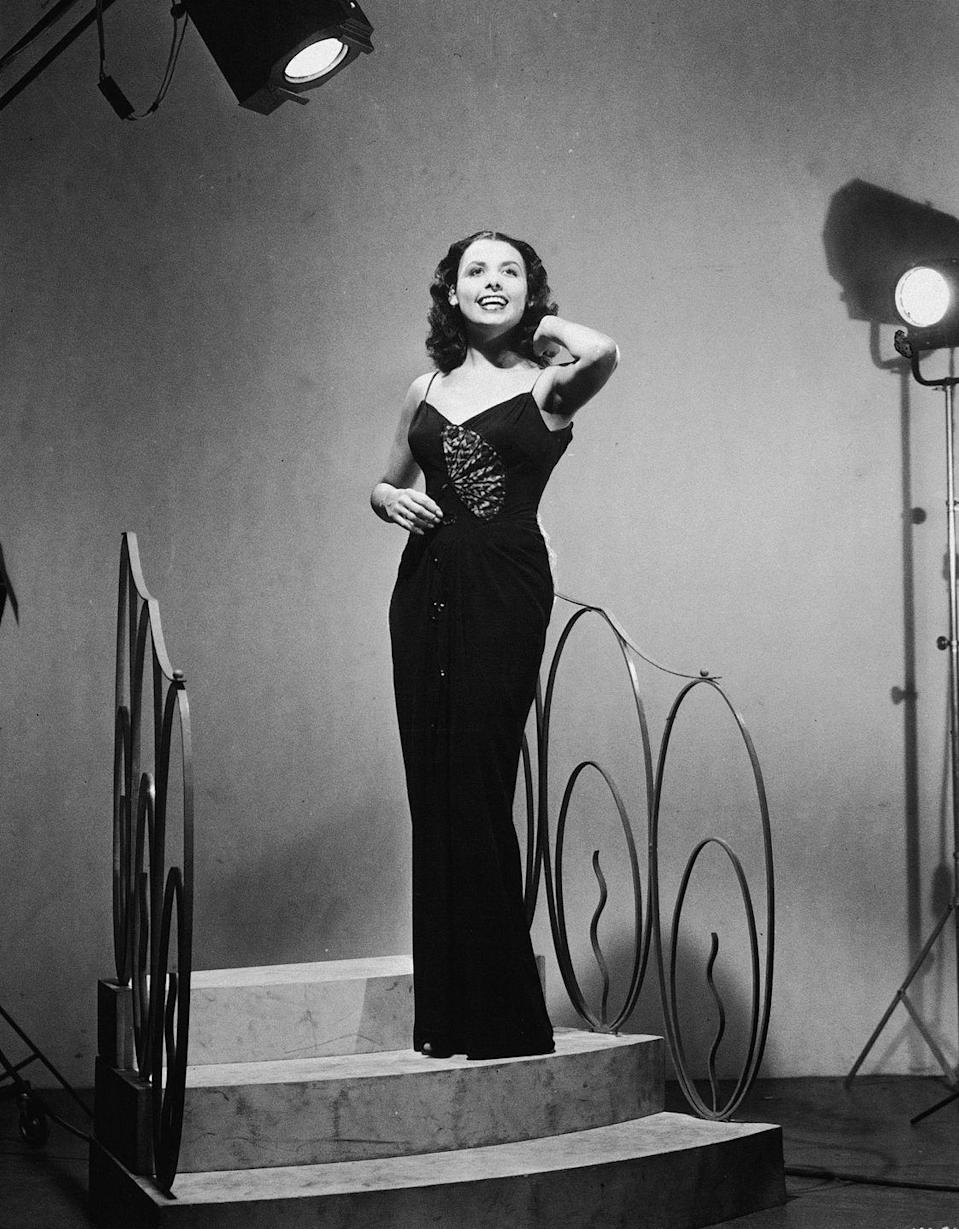 <p>Lena Horne sings on a stage set of stairs, wearing a floor-length column gown. </p>