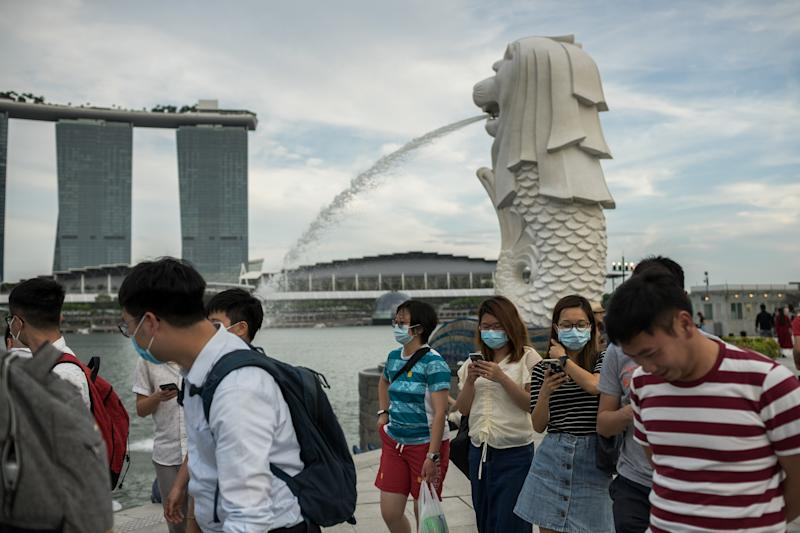 SINGAPORE - 2020/02/12: People wearing protective surgical masks walk along the Merlion Park, a major tourist attraction in Singapore. Singapore declared the Coronavirus outbreak alert as Code Orange on February 7, 2020. (Photo by Maverick Asio/SOPA Images/LightRocket via Getty Images)