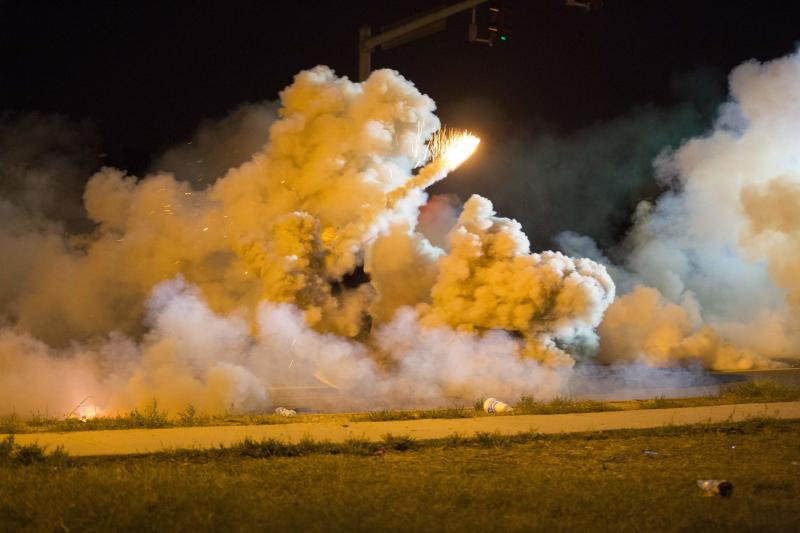A protester throws back a smoke bomb while clashing with police in Ferguson