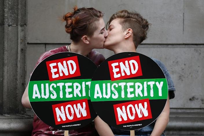 Anti-austerity demonstrators kiss outside the Bank of England as they wait for the start of the march in London on June 20, 2015 (AFP Photo/Justin Tallis)