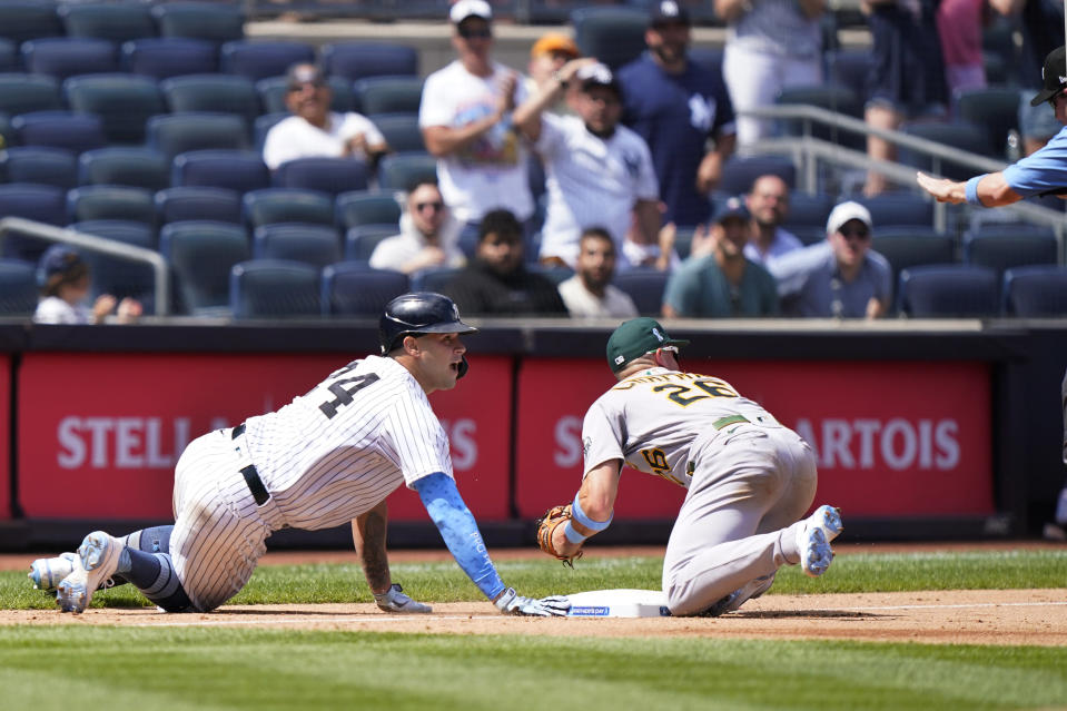 New York Yankees Gary Sanchez (24) and Oakland Athletics third baseman Matt Chapman (26) look toward the third base umpire after Sanchez advanced to third but overran the base on a throw home after hitting a two-run double during the sixth inning of a baseball game, Sunday, June 20, 2021, at Yankee Stadium in New York. Sanchez was safe after a review.(AP Photo/Kathy Willens)
