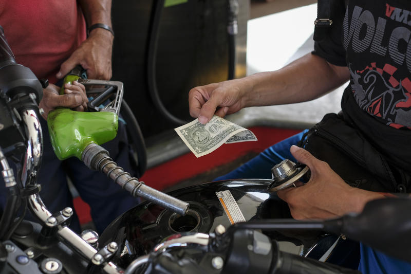 CARACAS, VENEZUELA - JUNE 26: A man pays with a one US dollar bill after filling his motorbike tank at a gas station on June 26, 2019 in Caracas, Venezuela. Everyday, more Venezuelans use American dollar notes to buy groceries, pay a hair cut or fill the tank of their cars and motorbikes. As IMF forecasts a 10 million percent inflation for 2019 in Venezuela, using dollars is a way to protect savings. Today, one US Dollar is worth 6,359 bolivares soberanos according to Venezuela Central Bank. Due to official restrictions, most people get dollars in the black market at higher rates. (Photo by Matias Delacroix/Getty Images)