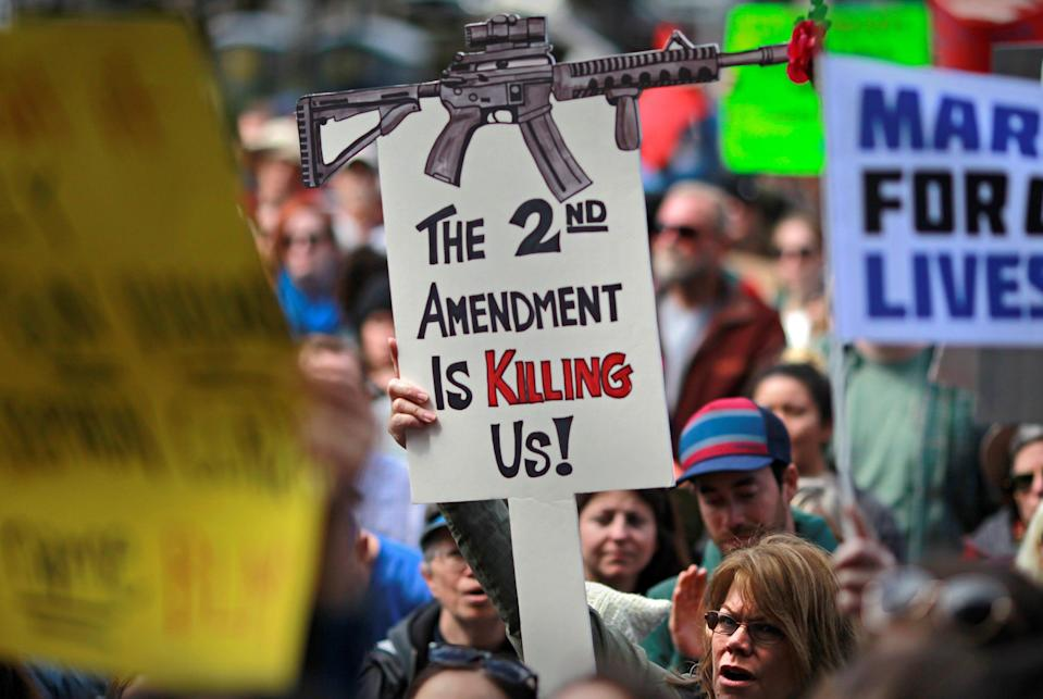 """Protestors hold signs during a """"March For Our Lives"""" demonstration demanding gun control in Sacramento, California, U.S. March 24, 2018."""