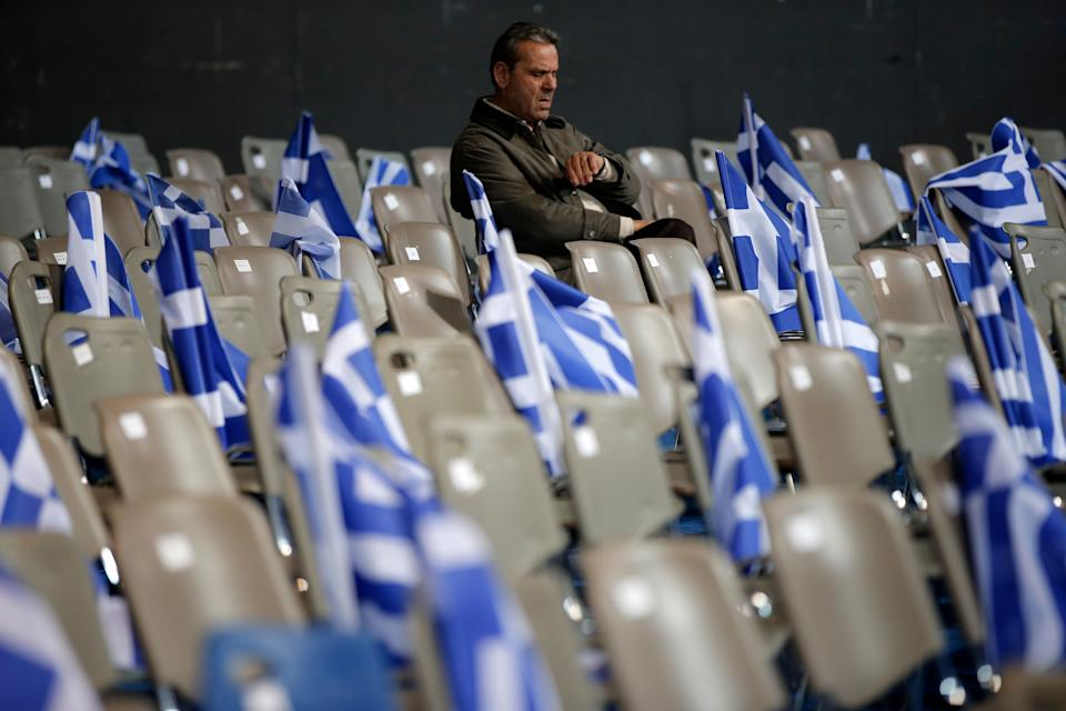 A supporter of New Democracy party, who denied to be identified, looks at his watch ahead of Prime Minister's Antonis Samaras pre-election speech at the Taekwondo Indoor Stadium in southern Athens on Friday, Jan. 23, 2015.  (AP Photo/Lefteris Pitarakis)