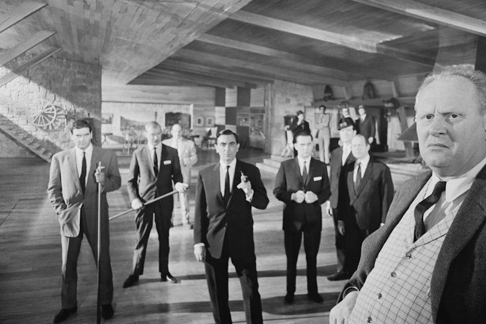 <p>Gert Fröbe as Auric Goldfinger, stands with a group of actors, as members of the Mafia, including actors Martin Benson and Bill Nagy, on the set of 'Goldfinger', 1964.</p>