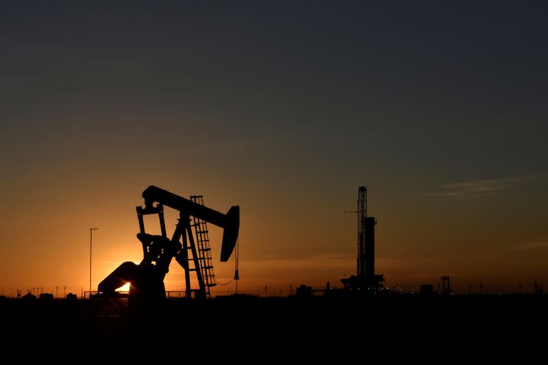 A pump jack operates in front of a drilling rig at sunset in an oil field in Texas