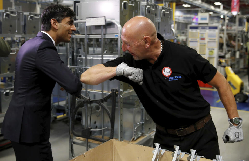 Britain's Chancellor of the Exchequer Rishi Sunak, left, greets an employee during a visit to Worcester Bosch factory to promote the initiative, Plan for Jobs, in Worcester, England, Thursday July 9, 2020. (Phil Noble/Pool via AP)