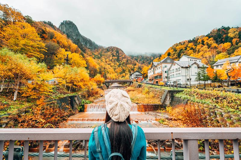 woman in a blue coat looking over a bridge at a forrest full of green, orange and yellow trees