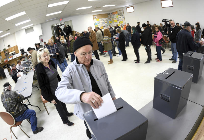 Serenus Hoffner, of Bismarck, North Dakota, places his ballet in the ballet box after voting at the North Dakota Democratic NPL Presidential Caucus at the AFL-CIO House of Labor in Bismarck, N.D., Tuesday, March 10, 2020.  (Mike McCleary/The Bismarck Tribune via AP)